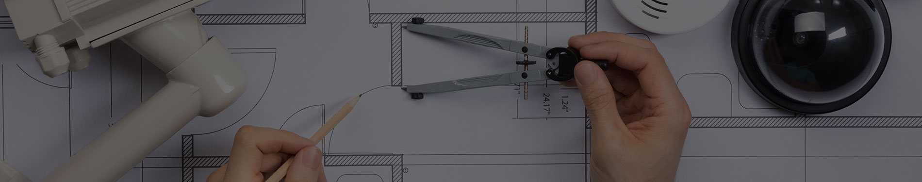person using pencil and compass to design building plans