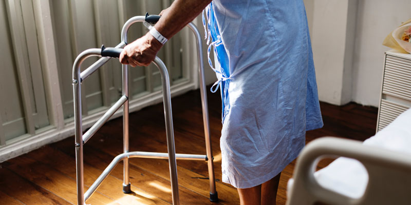 hospital patient getting out of bed with walker